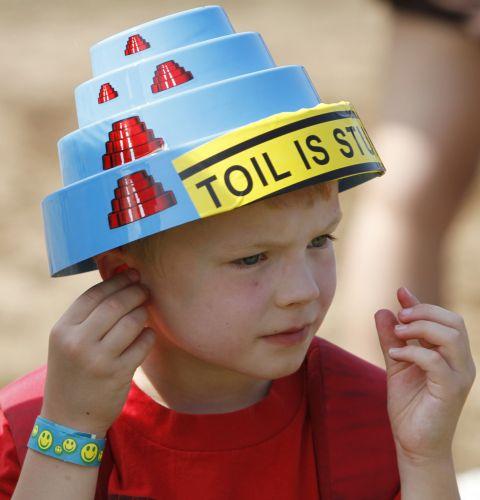 O menino Andrew Burke, 6, de Chicago, coloca seus protetores de ouvido durante o show do Devo no festival Lollapalooza (06/08/2010)