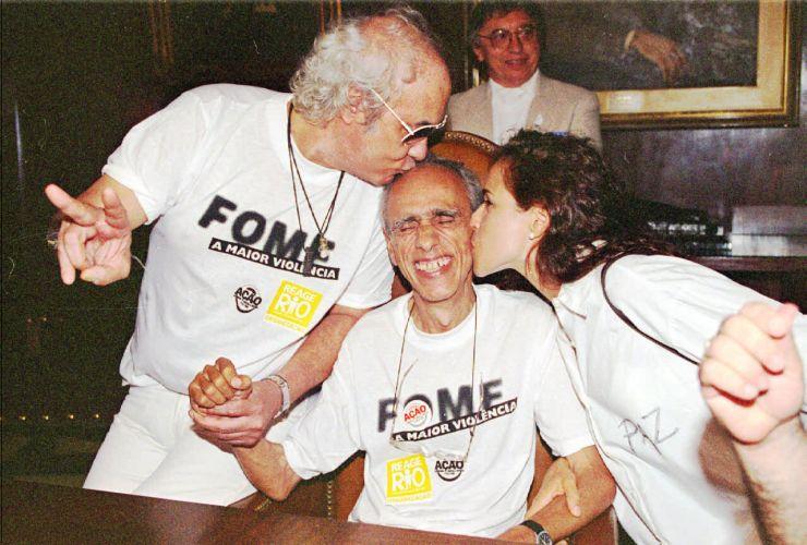 Erasmo Carlos e Daniela Mercury beijam o sociólogo Herbert de Souza, o Betinho, durante a passeata do movimento Reage Rio (29/11/1995)