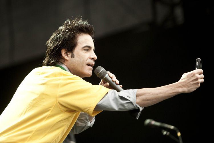 Usando uma camiseta da seleção brasileira e fazendo fotos do público, o vocalista da banda Train, Pat Monahan, sobe ao palco do Pop Music Festival, em São Paulo (19/03/2011)