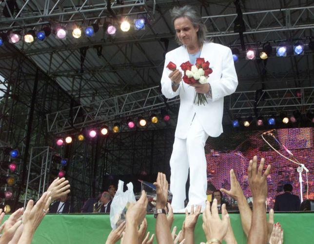 O cantor Roberto Carlos joga rosas para o público durante show em comemoração ao aniversário de São Paulo, na praça da Paz, no parque Ibirapuera (25/01/2001) A música de Roberto Carlos marcou sua vida? Clique no link ao final da legenda e conte sua história