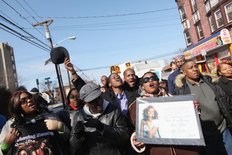 Fãs de Whitney Houston cantam em homenagem à cantora nas proximidades da igreja batista New Hope, em Newark, nos EUA