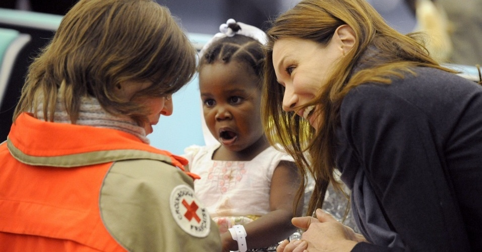 No aeroporto de Roissy, em Paris, Carla Bruni (dir.) dá boas vindas às 33 crianças haitianas que chegaram ao país para serem adotadas por famílias francesas (22/1/10)