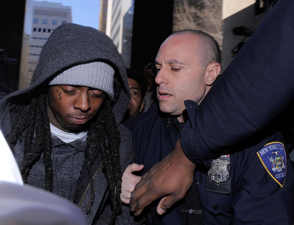 O rapper Lil Wayne (esq.) é cercado por policiais na entrada de tribunal de Nova York (8/3/2010)