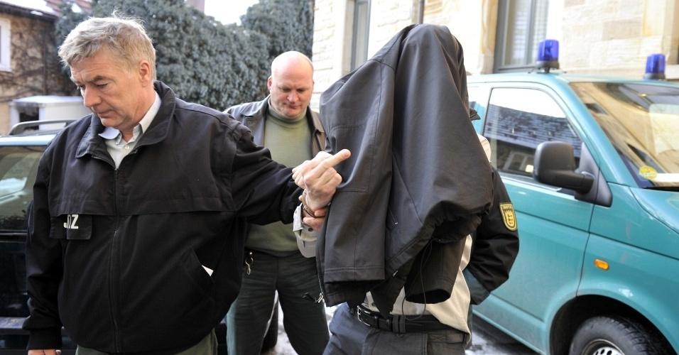 Edis 'Eddie' Kayalar esconde o rosto e faz gesto obceno para a imprensa ao chegar a tribunal, onde foi julgado por extorquir dinheiro da supermodelo Cindy Crawford, em Kirchheim, na Alemanha (9/3/2010)
