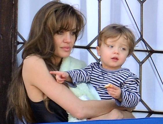 Em varanda de casa em Veneza, Angelina Jolie observa a vista com o filho Knox no colo. Ao lado, Shiloh Jolie-Pitt (23/3/2010)