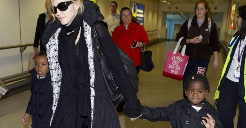 Madonna desembarca com os filhos no aeroporto de Londres. À direita, Mercy James, acena para os fotógrafos (29/3/2010)