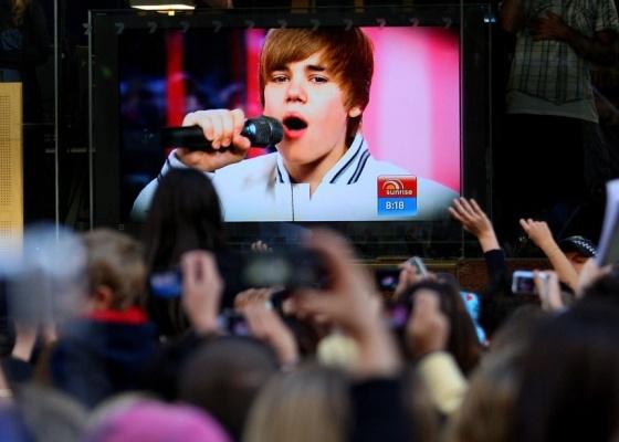 Fãs assistem performance do cantor Justin Bieber por um telão em Sydney, na Austrália (26/4/2010). O show, que seria do lado externo, teve de ser cancelado após mais de 5 mil pessoas acamparem desde o dia anterior, e diversas jovens se machucarem no meio da multidão