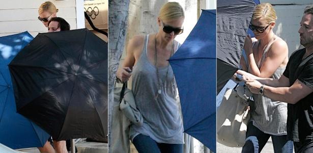 A atriz Charlize Theron se esconde atrás de dois guarda-chuvas ao sair de academia em Beverly Hills (28/4/2010)