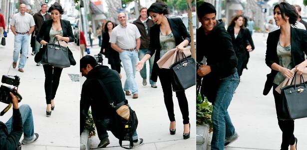 Kim Kardashian tenta ajudar um fotógrafo que caiu enquanto andava de costas fotografando-a, em Beverly Hills (27/4/2010)