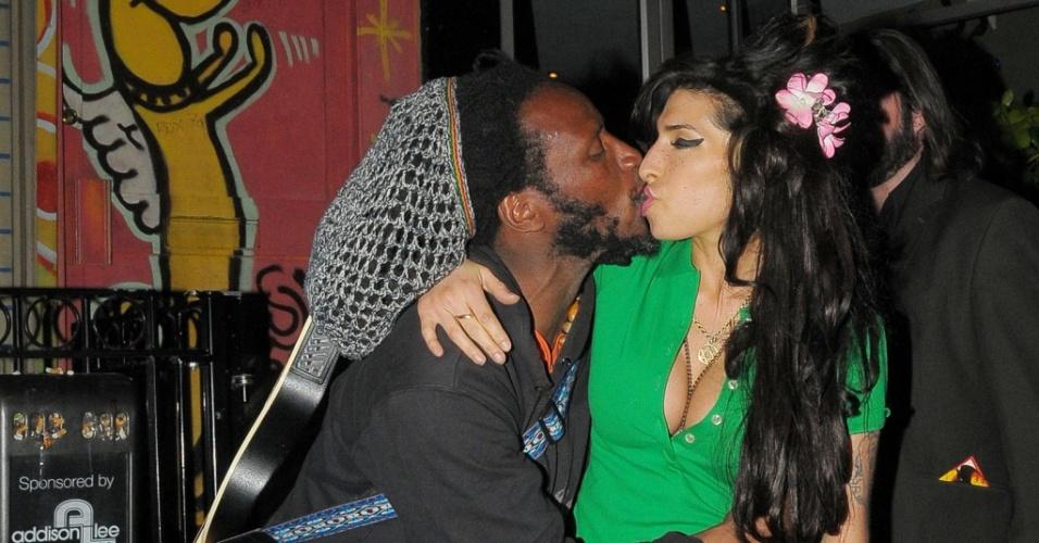 Amy Winehouse dá selinho em amigo na saída de clube em Londres (27/4/2010)