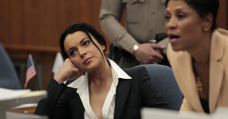 A atriz Lindsay Lohan (esq.) ao lado de sua advogada Shawn Chapman Holley (dir.) durante audiência no tribunal de Beverly Hills, na Califórnia (24/5/2010)