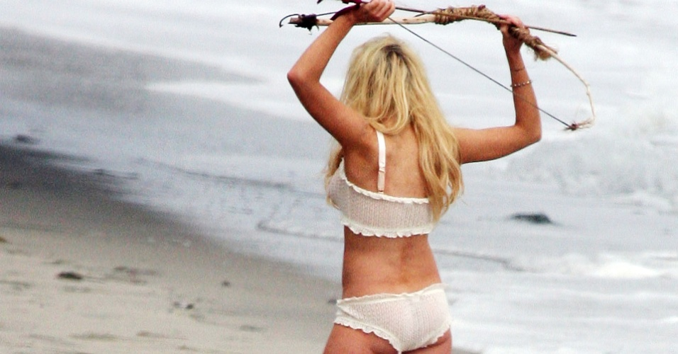 A atriz Lindsay Lohan posa de lingerie e com um arco e flecha em praia de Malibu (5/6/2010)