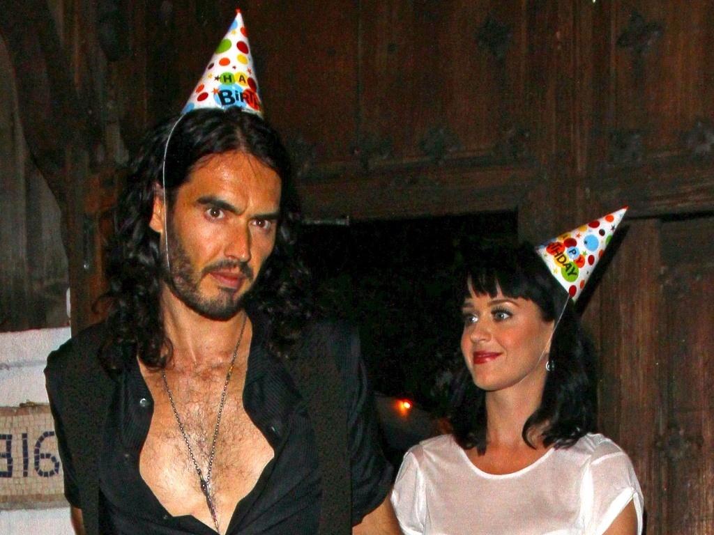 O humorista Russell Brand e a cantora Katy Perry usam chapéus de aniversário na festa de 35 anos do ator em restaurante de Los Angeles (4/6/2010)