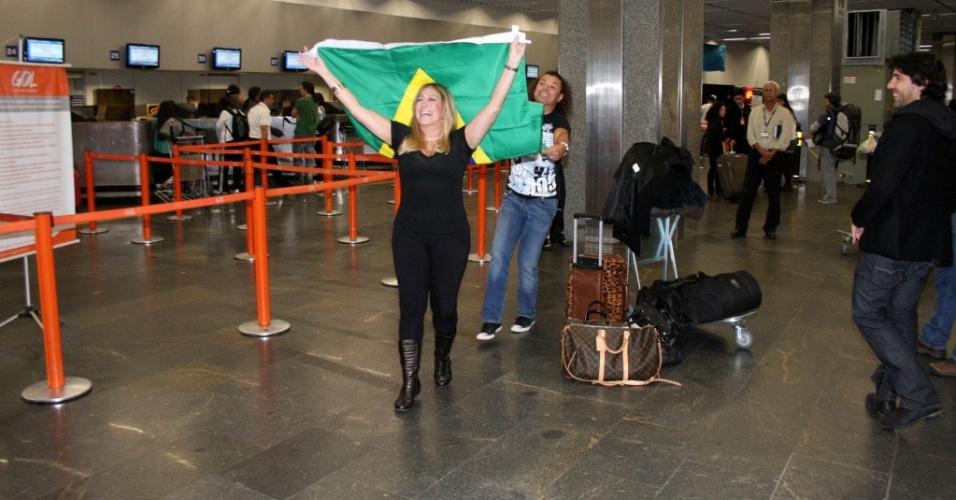 A atriz Susana Vieira desfila com a bandeira do Brasil pelo aeroporto internacional do Rio. Ao fundo, David Brazil (7/6/2010)