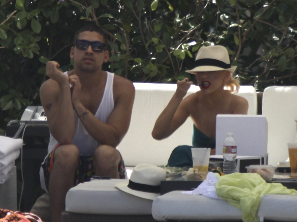 A cantora Christina Aguilera come na beira de uma piscina em Miami (12/6/2010)