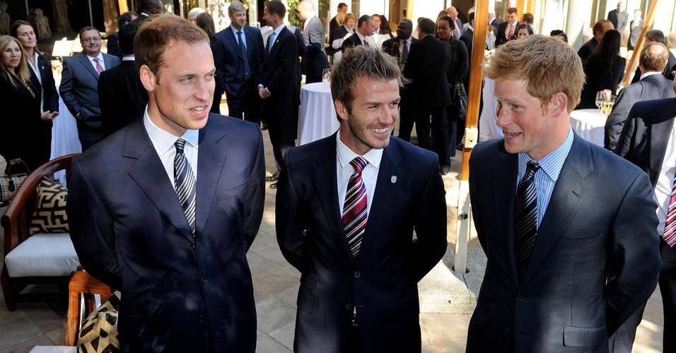 Príncipe William (à esq.) conversa com o jogador de futebol David Beckham e com o Príncipe Harry (à dir.) durante uma festa em um hotel de Johannesburgo, África do Sul, no sábado (19/6/2010)