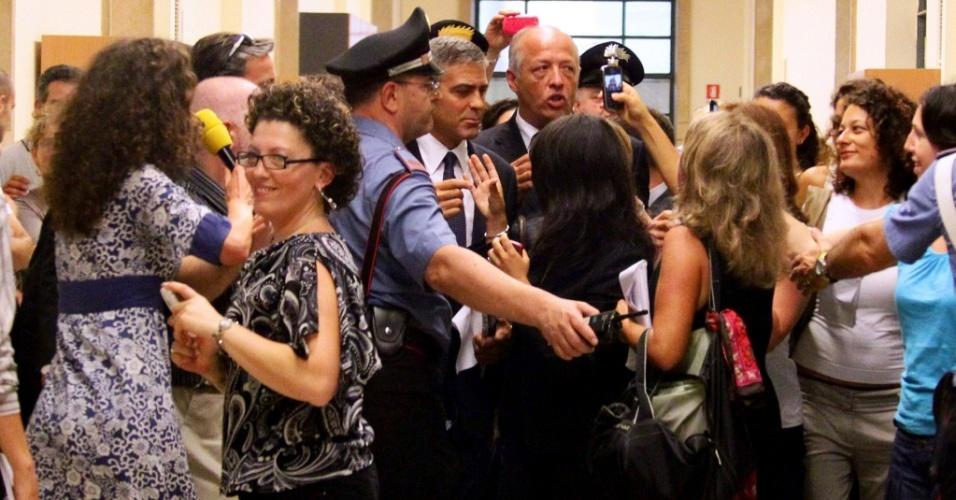 O ator George Clooney cercado por fãs e imprensa em tribunal em Milão, na Itália (16/7/2010)