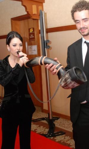 A cantora Sandy toca um berrante para o repórter do