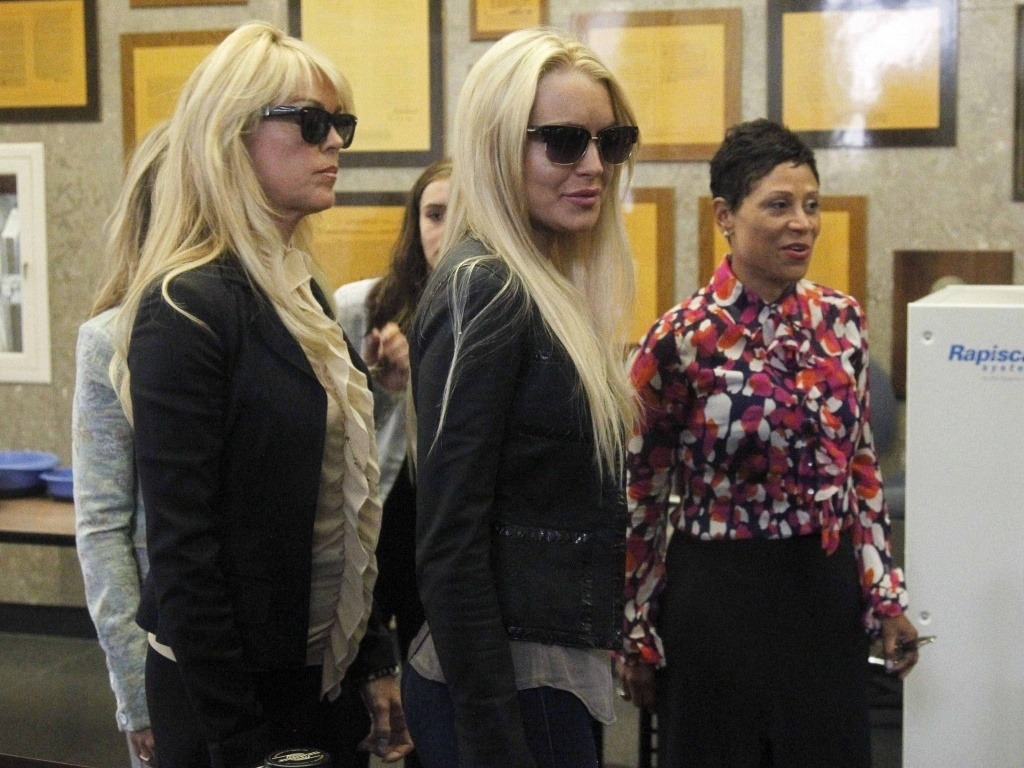 A atriz Lindsay Lohan (ao centro) chega ao tribunal de Beverly Hills para se entregar  polcia, acompanhada da me, Dina Lohan (esq.), e da advogada Shawn Chapman Holley (dir.) 