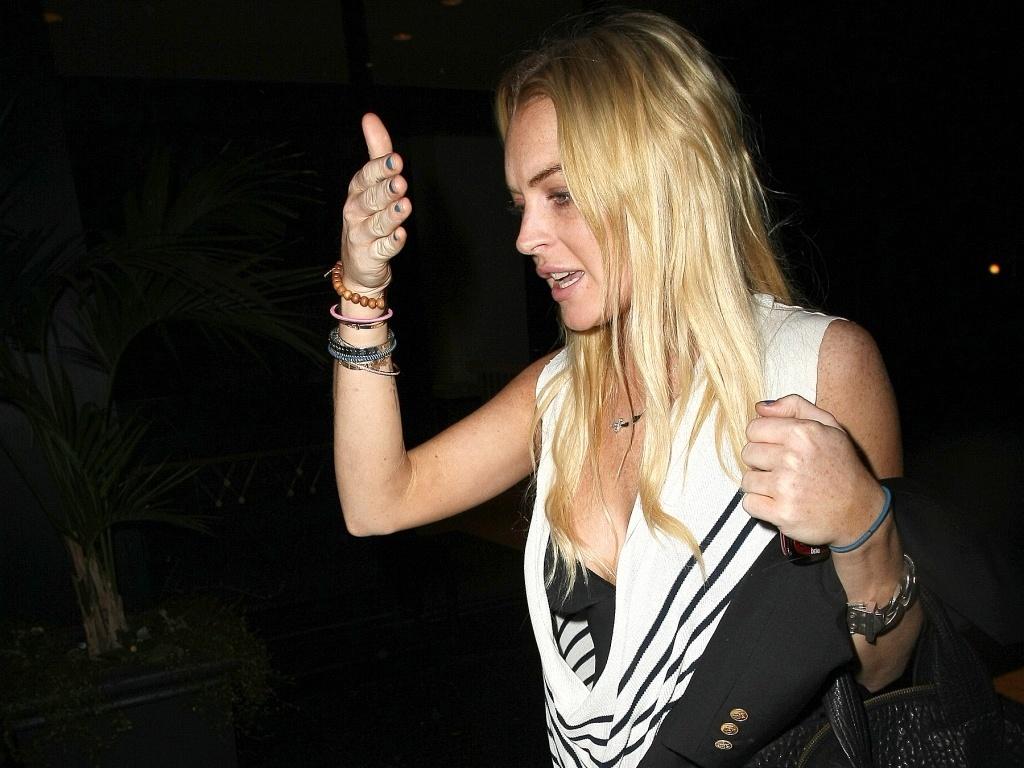 A atriz Lindsay Lohan tenta se esconder dos paparazzi na chegada a hotel em Beverly Hills (31/8/2010)