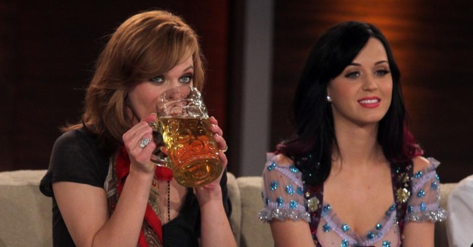 Milla Jovovich toma Fassbier ao lado de Katy Perry durante a participação na 190ª edição do talkshow alemão