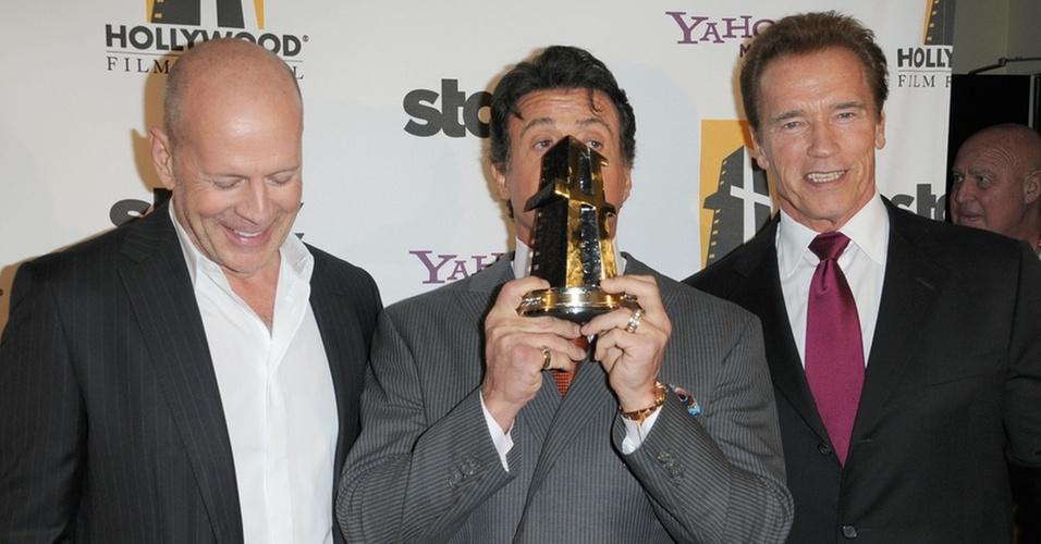 Ao lado de Bruce Willis (esq.) e Arnold Schwarzenegger (dir.), Sylvester Stallone beija prêmio de homenagem em Beverly Hills (24/10/2010)
