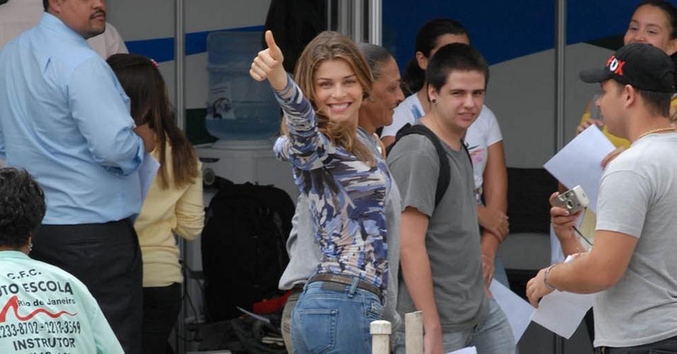 Grazi Massafera acena para os fotógrafos durante exame para tirar a carteira de habilitação, no Rio (27/10/10)