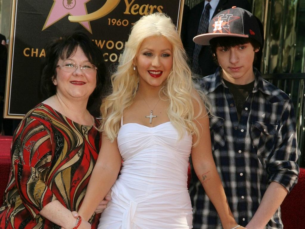 Ao lado da mãe e do irmão, Christina Aguilera posa ao lado de sua estrela na calçada da fama de Hollywood em Los Angeles (15/11/2010)