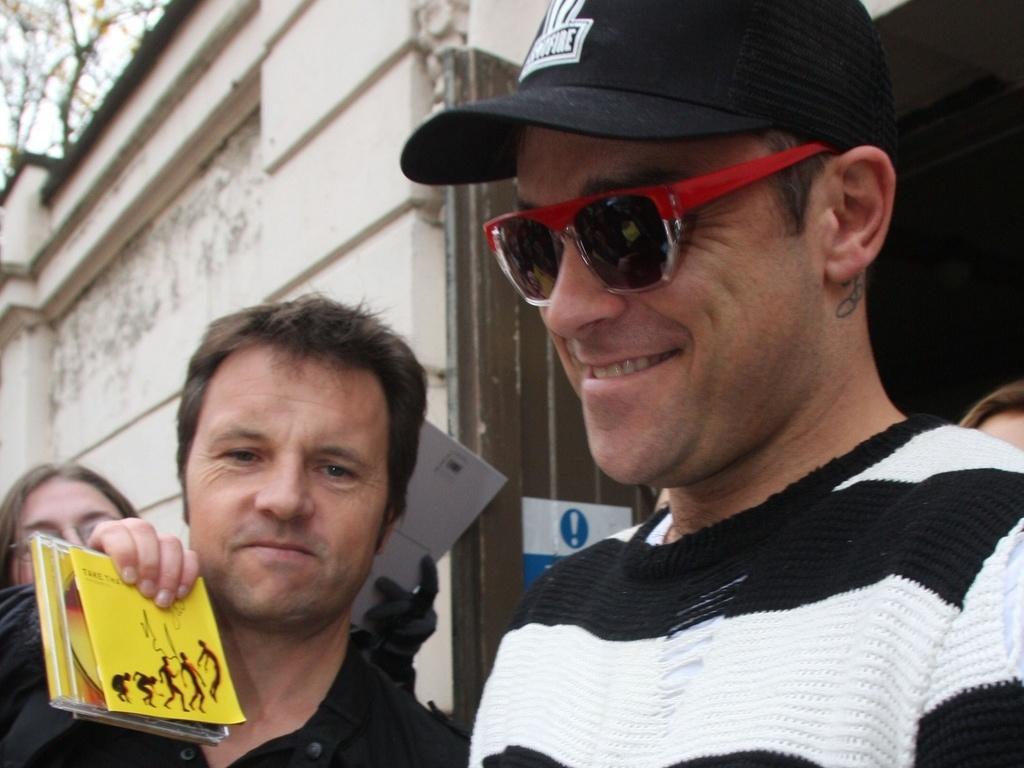 Robbie Williams autografa sua versão em boneco para fã ao sair de estúdio em Londres (22/11/2010)