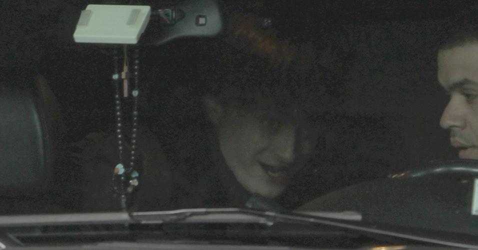 O ator Daniel Radcliffe tenta se esconder dos paparazzi ao entrar no carro na saída de seu apartamento em Nova York (6/1/2011)