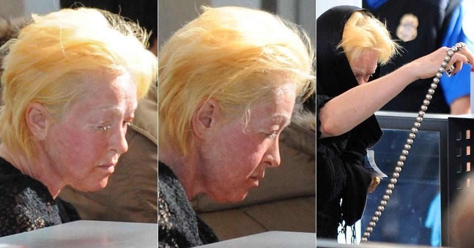 Com o rosto vermelho e a pele bastante irritada, a cantora Cyndi Lauper embarca no aeroporto de Los Angeles (31/1/2011)