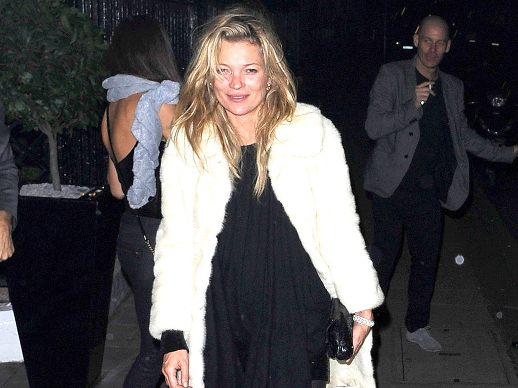 Kate Moss sorri aparentemente bbada na sada de um clube noturno em Londres (6/2/2011)