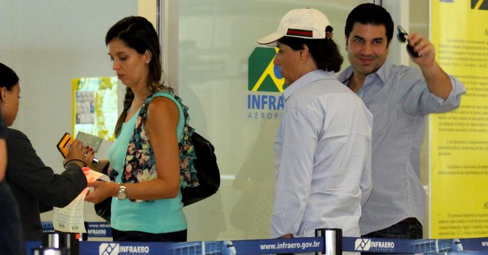 Acompanhado de Tom Cavalcante e sua mulher Patricia, o apresentador Edu Guedes acena para fãs ao embarcar no aeroporto Santos Dumont, no Rio de Janeiro (14/2/2011)
