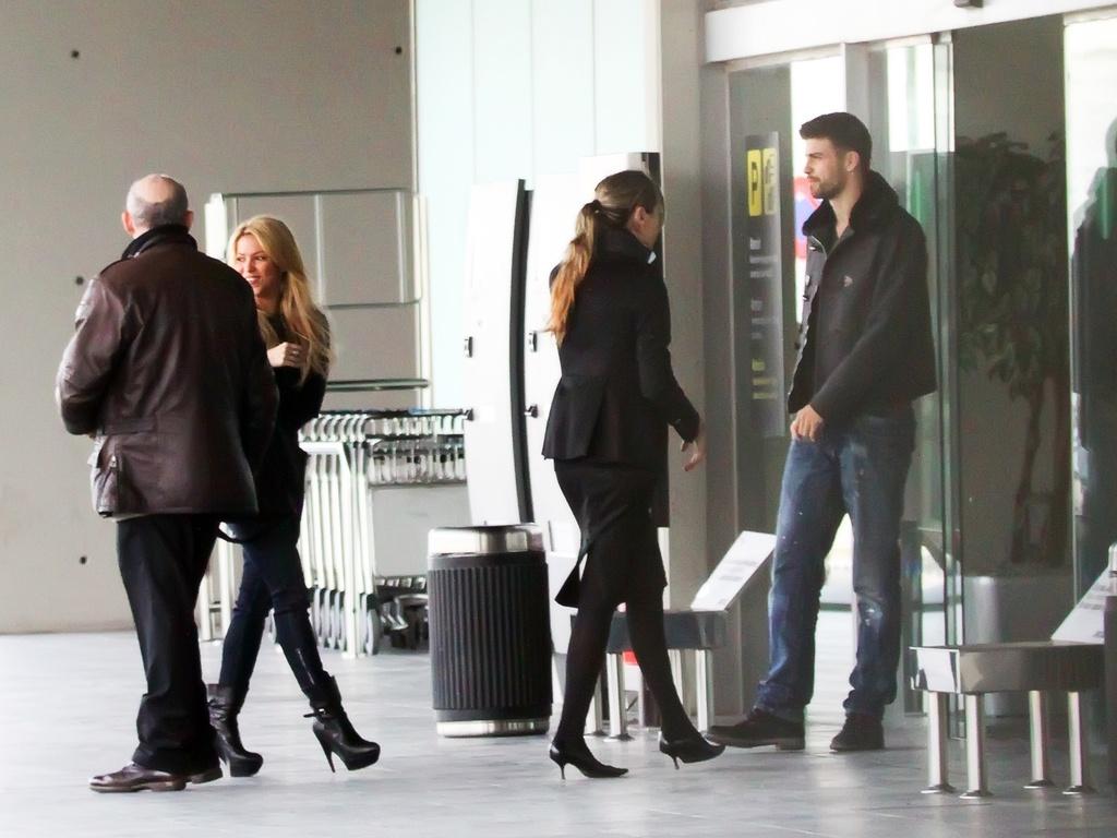 Aumentando ainda mais os rumores de que estão namorando, a cantora Shakira (esq.) e o jogador de futebol Piqué (dir.) são vistos juntos com um grupo de pessoas no aeroporto de Barcelona (21/2/2011)