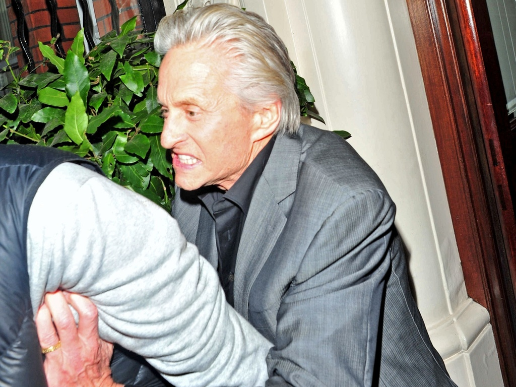 Michael Douglas empurra um fotgrafo na porta de hotel em Londres (24/2/2011)