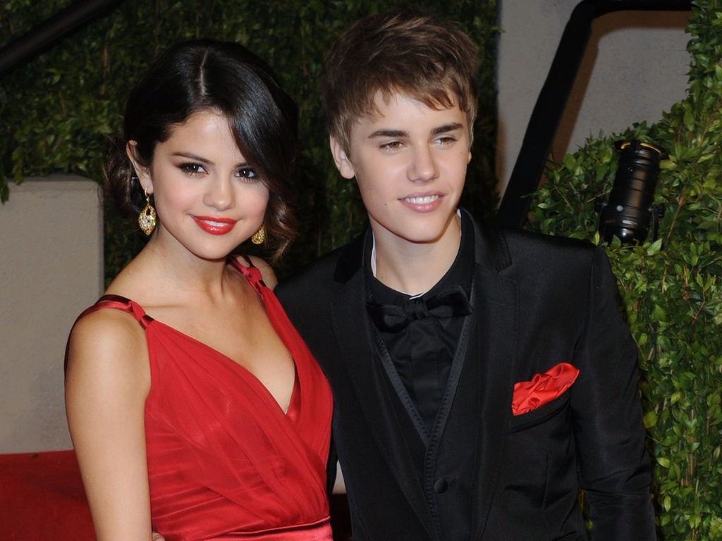 Selena Gomez e Justin Bieber posam abraados no tapete vermelho da festa da revista 