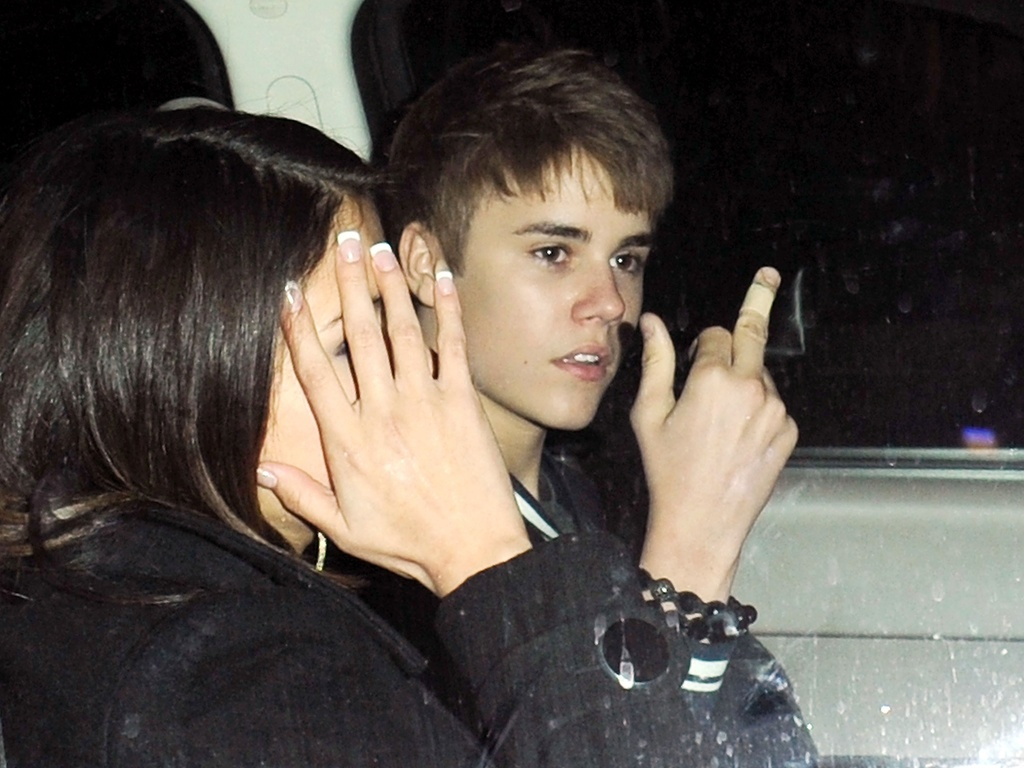 Justin Bieber mostra o dedo mdio ao lado da atriz Selena Gomez, que esconde o rosto, na sada do aniversrio do cantor, em Los Angeles (1/3/2011)