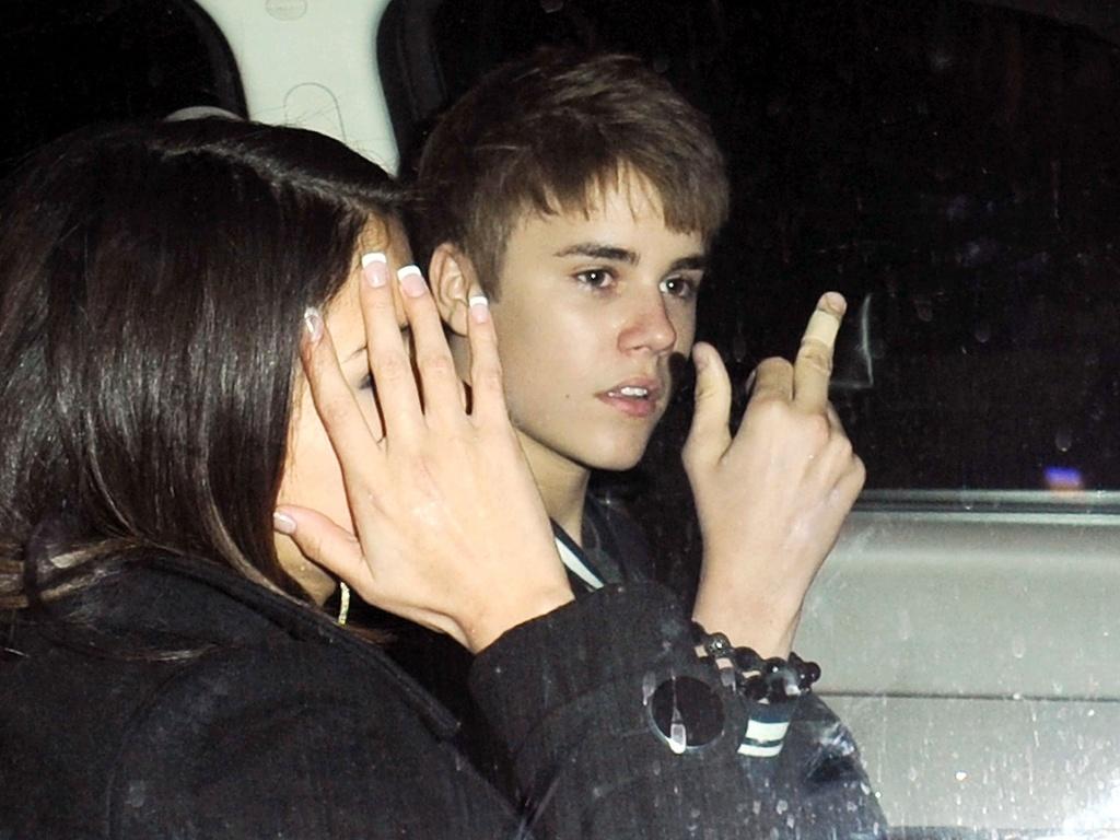 Justin Bieber mostra o dedo médio para os fotógrafos na saída de um restaurante, no dia de seu aniversário, ao lado de Selena Gomez, em Los Angeles (1/3/2011)