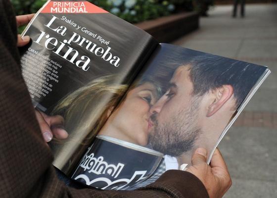 Homem olha revista Caras colombiana que traz fotos de Shakira e Piqu� se beijando durante festa em Barcelona, em Bogot� (14/3/2011)
