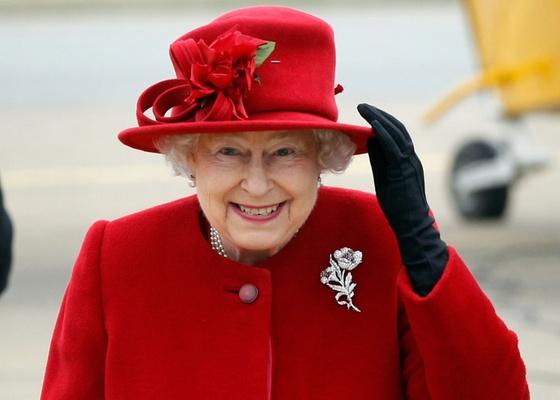 Rainha Elizabeth segura o chapéu ao chegar à base da ilha de Anglesey, em Gales, em visita ao neto príncipe William (1/4/2011)