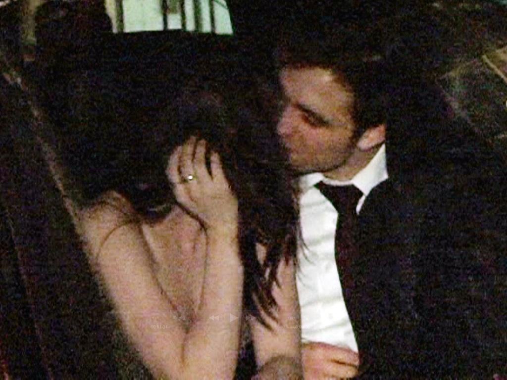 Os atores Kristen Stewart e Robert Pattinson se beijam no banco traseiro de um carro na saída da festa do filme