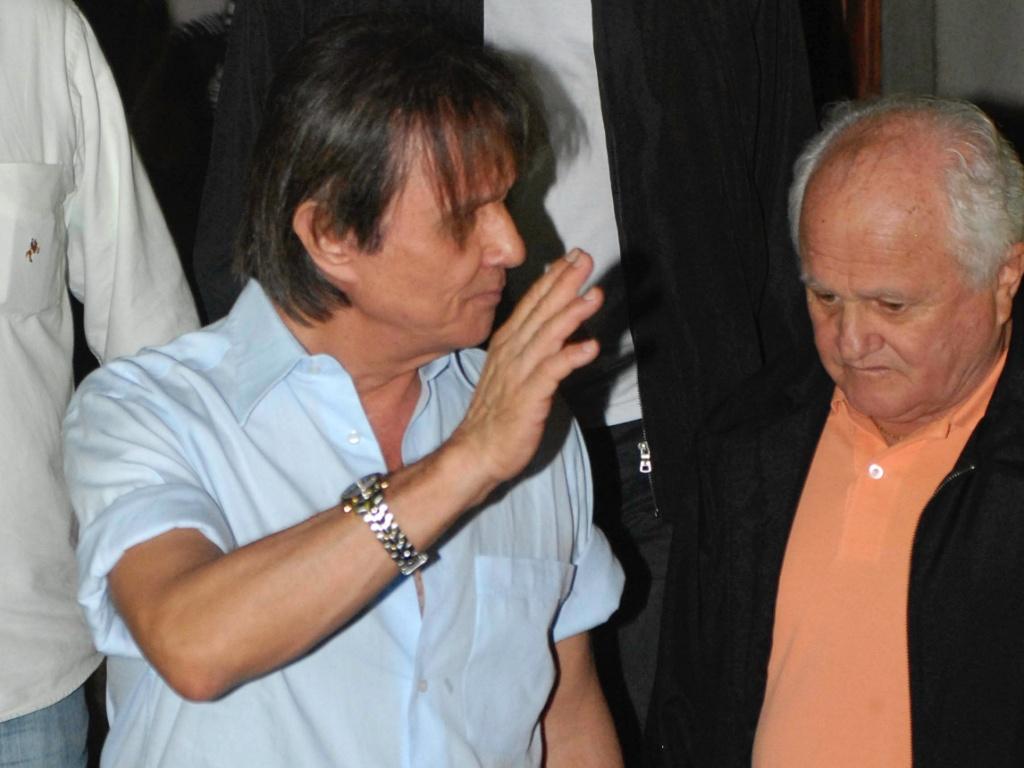 Roberto Carlos acena para fãs na saída da missa de sétimo dia da filha Ana Paula, em São Paulo (25/4/2011)