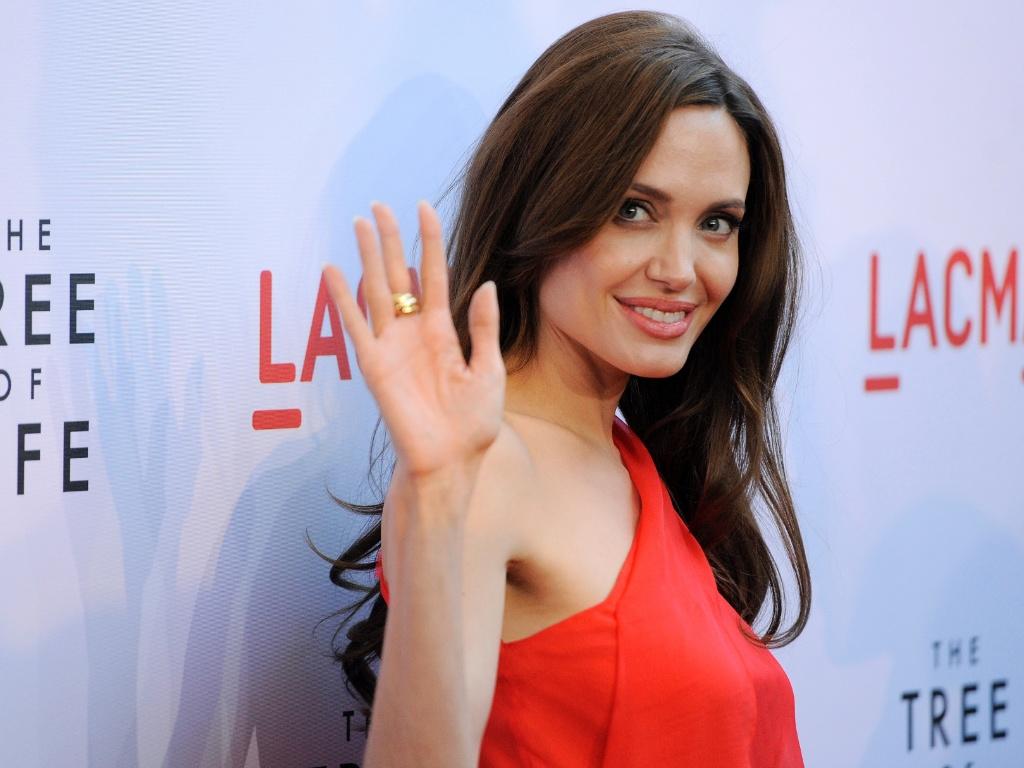 Angelina Jolie acena para fotógrafos no tapete vermelho da première de