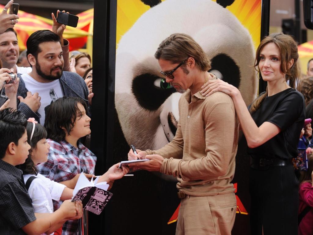 Angelina Jolie faz companhia a Brad Pitt enquanto o ator atende fãs na première de