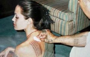 Angelina tatua uma prece budista simbolizando seu filho Maddox, em Bancoc, na Tailândia. Essa tattoo cobriu o símbolo japonês da morte (23/04/2003)