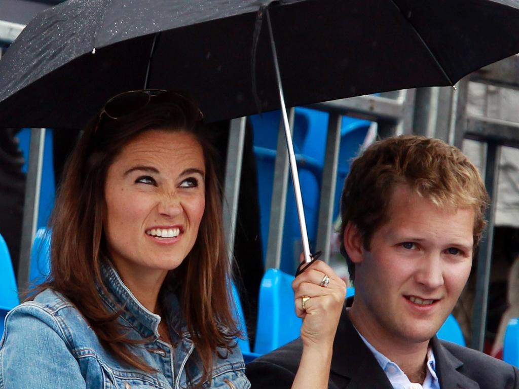 Pippa Middleton e George Percy se protegem da chuva durante pausa em jogo do Torneio de Queens, em Londres (9/6/2011)
