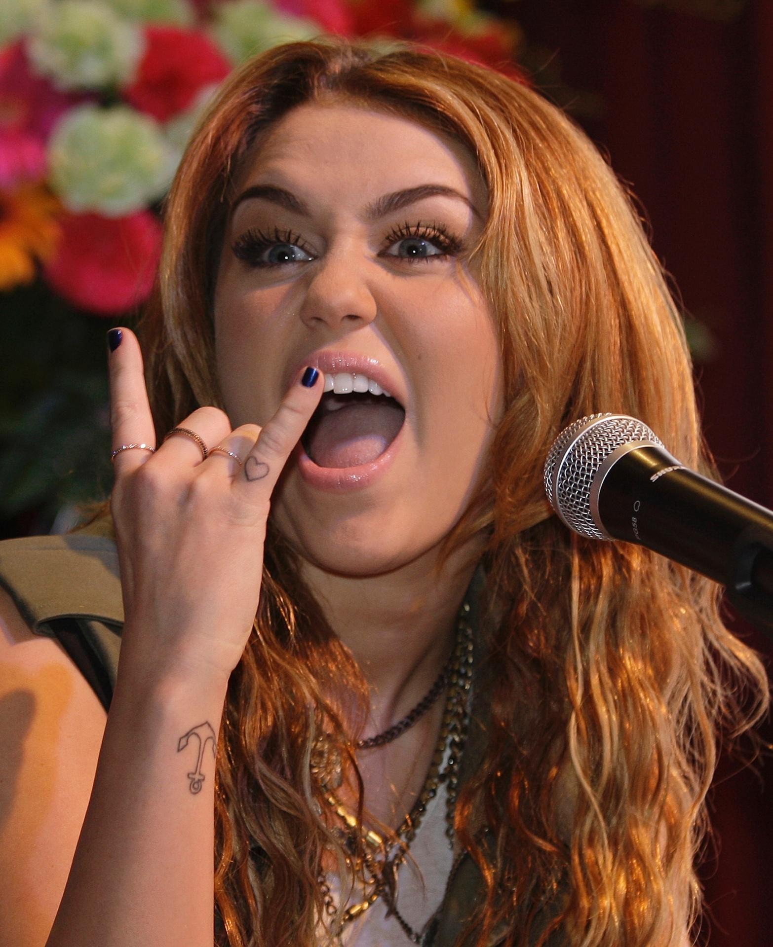 Miley Cyrus faz pose de roqueira e cumprimenta os fãs nas Filipinas (16/6/11)