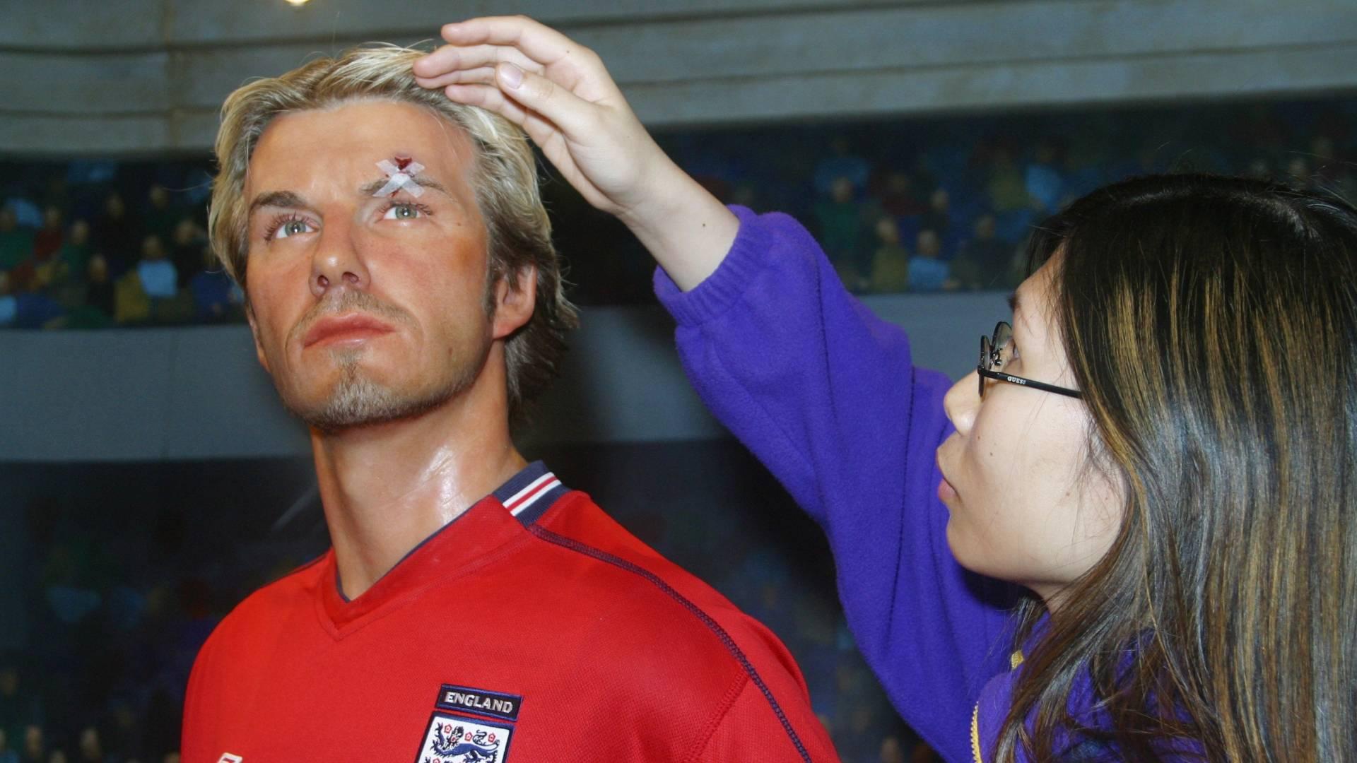 Funcionária do museu Madame Tussauds de Hong Kong arruma o cabelo da figura de cera do jogador David Beckham (20/2/2003)