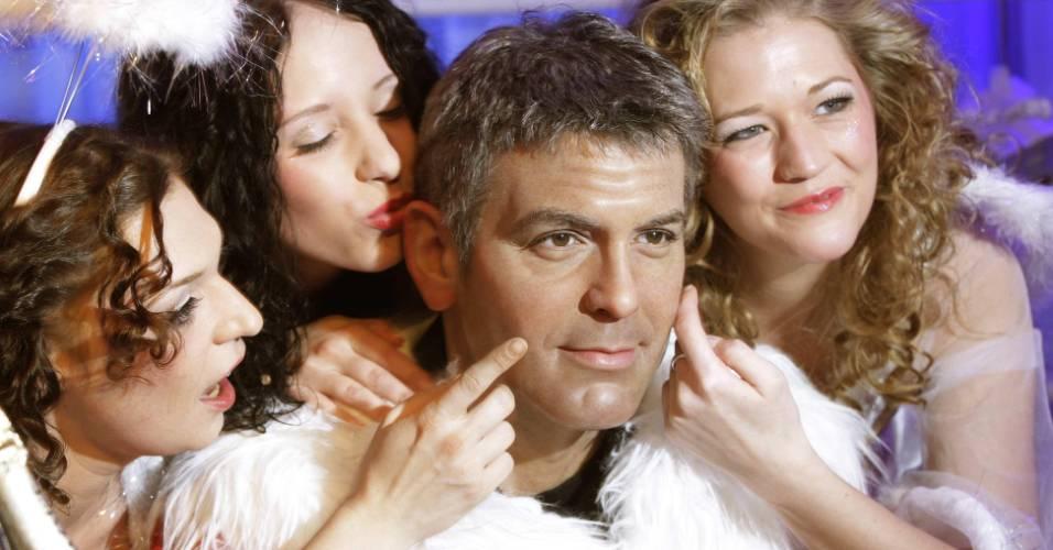 Modelos vestidas de anjos de Natal fazem graça com a figura de cera do ator George Clooney, vestido de Papai Noel, no museu Madame Tussauds de Berlim (5/12/2008)