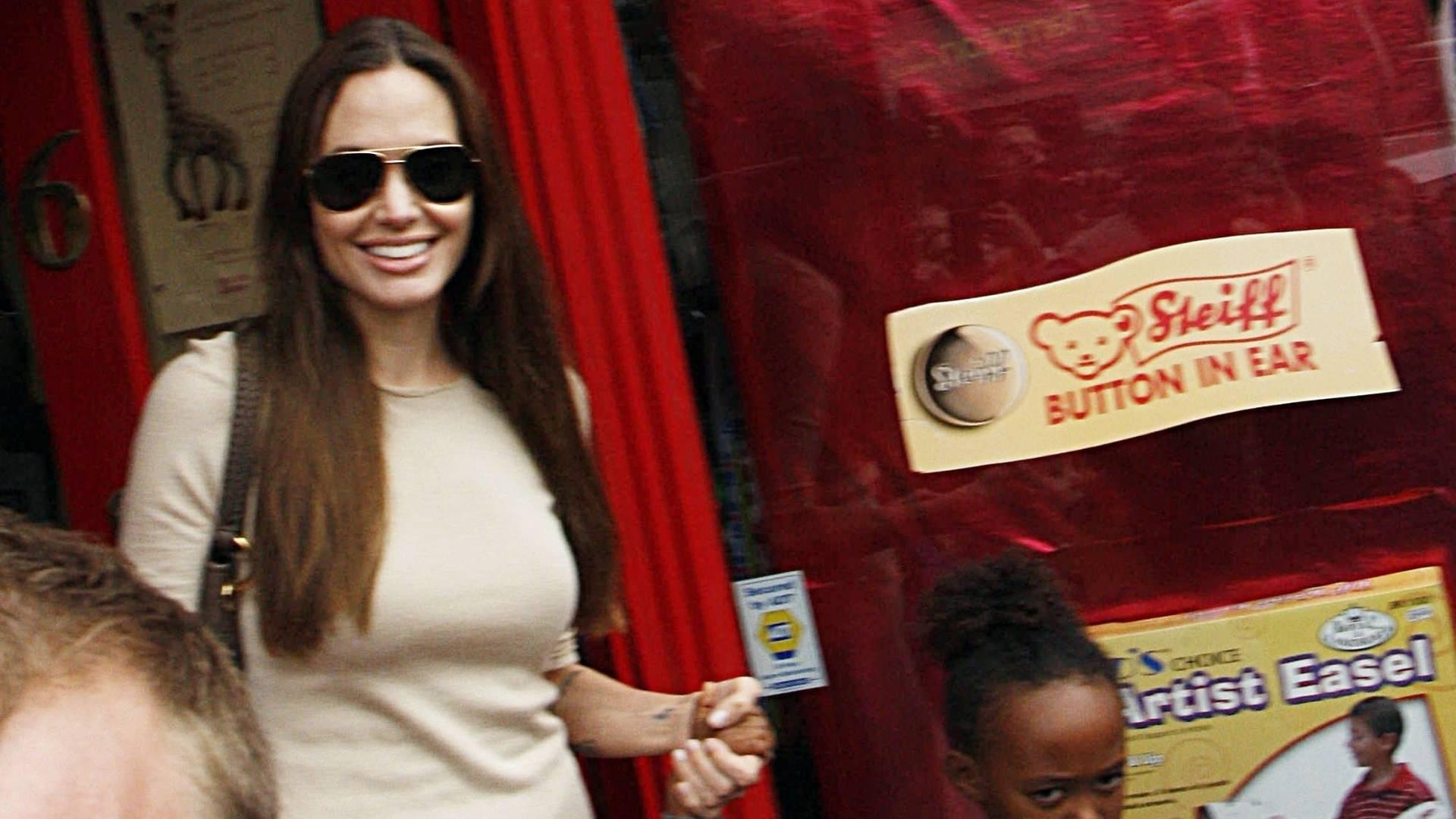 A atriz Angelina Jolie é cercada por fãs e fotógrafos ao levar as filhas Shiloh (esq.) e Zahara a uma loja de brinquedos em Richmond, no sudoeste de Londres (26/7/11)
